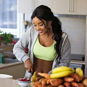 jeune femme coupant des fruits