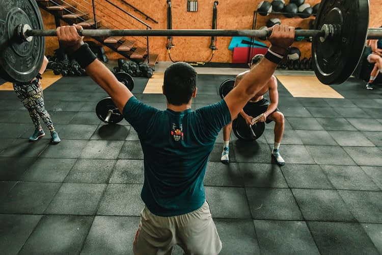 sportif levant un haltère au-dessus de sa tête